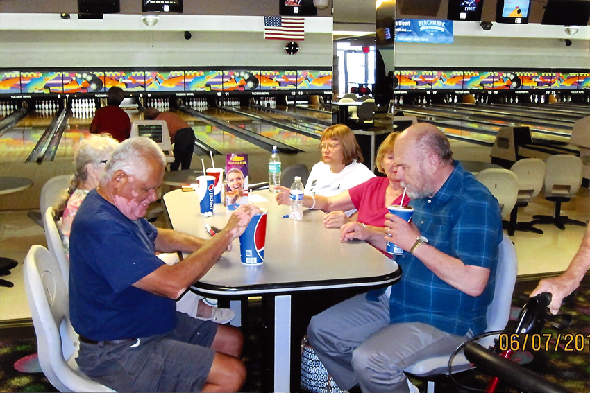 Joe and others at the Bowling Alley, sitting at a table drinking refreshments.