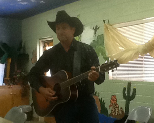 Brian Trask sings Country Oldies with guitar in hand and is dressed in black, naturally with a black cowboy hat too.
