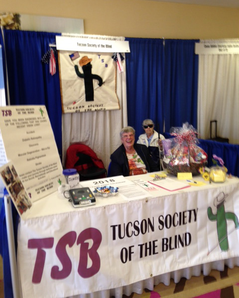 Members of Tucson Society of the Blind at the Tucson Expo Booth.  The organizations mascot, Timonthy hangs in the background, and information about the group sits on the table at the left and a gift basket at the right.