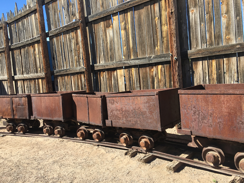 Coal cars are lined up on a piece of track, representing a valuable cash resource for many western settlers.