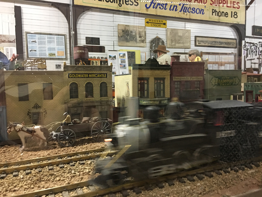 Model trains and buildings of early Tucson.  Depicts downtown with train moving into view.