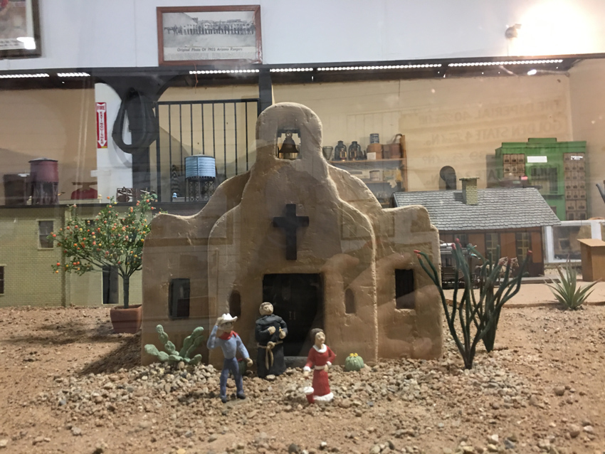 Model trains and buildings of early Tucson.  Depicts Presideo Church and persons standing.