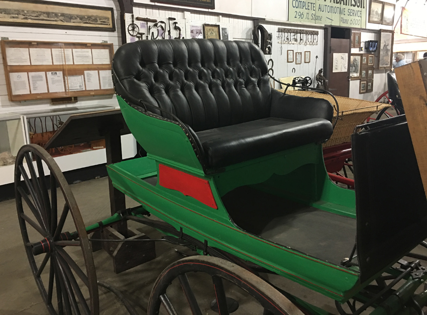 Basic carriage with black leather seats and green body.