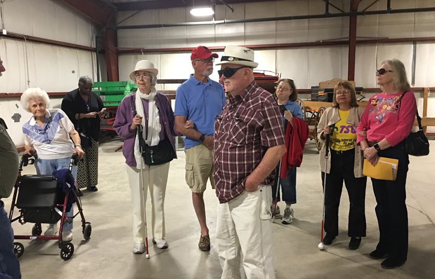 Members of TSB listen as our docent speaks about a carriage at the Rodeo Parade Museum.