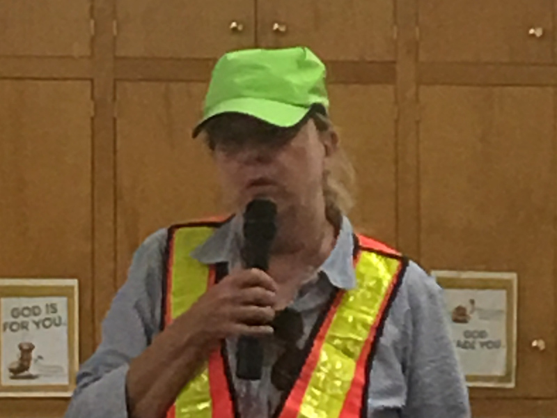 Orientation and Mobility instructor Suzi Gunn describes several safety tips for vision impaired and blind pedestrains.  She wears a bright neon green baseball cap and reflective orange and yellow safety vest which provides additional visility to drivers.