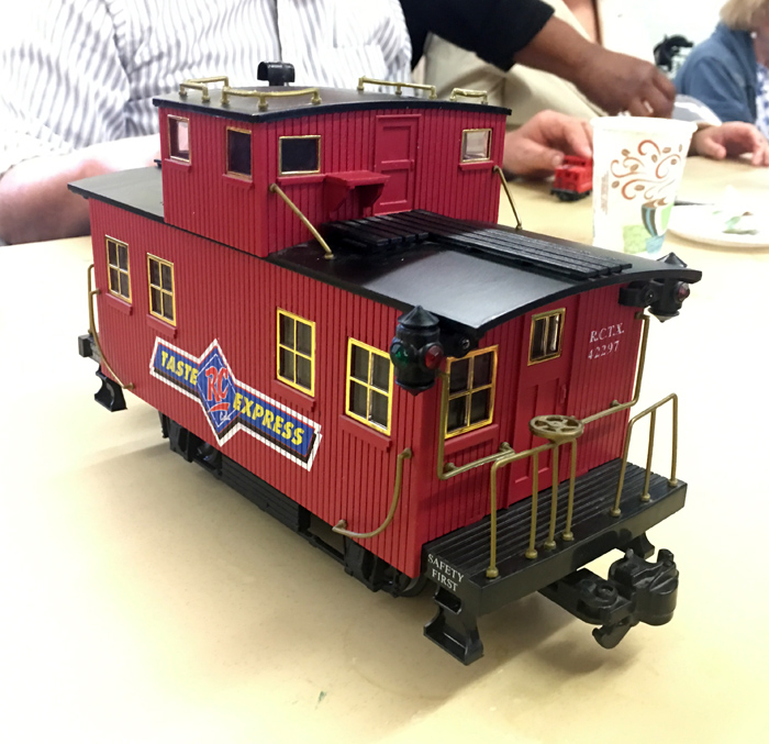 A replica of a cabboos similar to the Lincoln Memorial Train at 1/50 scale. Painted with red-brown paint and a dark brown roof.  Imprinted on the side is the logo for Taste Express.