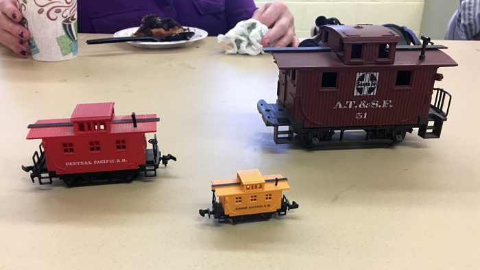 Three sizes of model cabbooses similar to the Lincoln Memorial Train, in front a yellow N gauge that can fit in ones hand, at the left a red HO guage model about the size of a half can of soda, and at the right a much larger brown O guage cabboos train that is the size of a package.