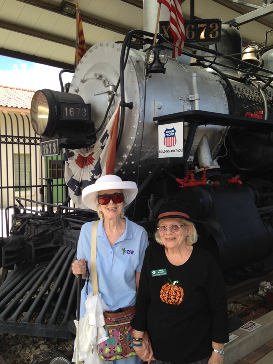 Annie and Carol pose at the front of all black steam engine at the Transportation Museum