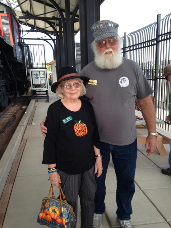 Carol poses with the Docent on the Transportation Museum platform next to the freight and passenger tracks where trains frequently roll by.