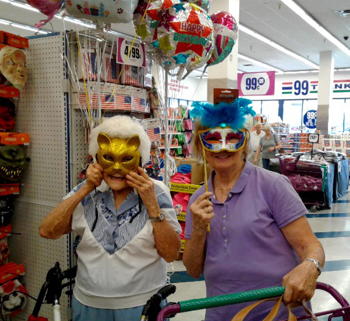 Wilma and Vickie show off their new masks at the Dollar Store with inflated balloons in the backround along with 99 cents signs hanging from the ceiling.